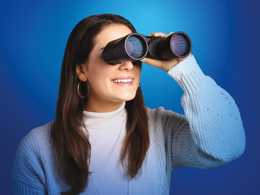 Woman looking through binoculars, course selections reflected in the lens